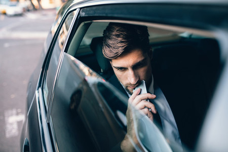 Male business executive travelling by a cab