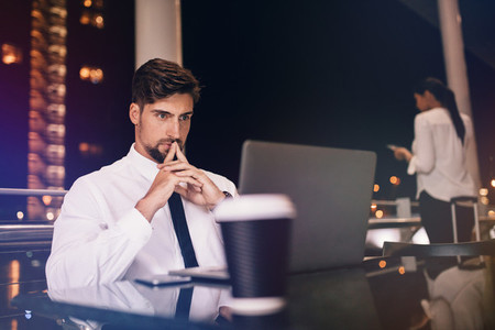 Businessman with laptop in modern airport lounge