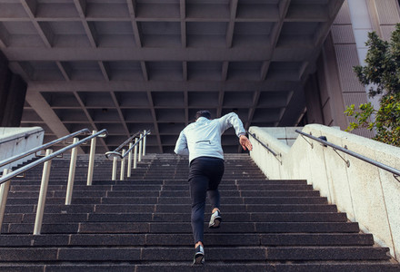 Back view of man running up the stairs