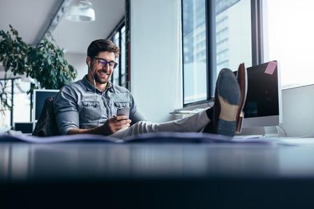 Male designer listening music during break