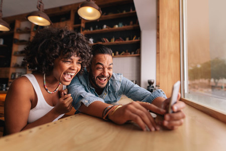 Young couple laughing and taking selfie in cafe