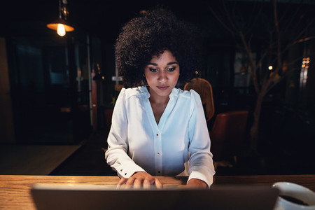 Businesswoman working late on laptop in office