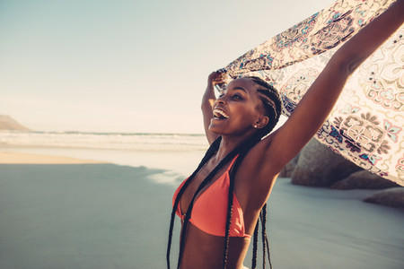 African woman enjoying on the beach with flying scarf