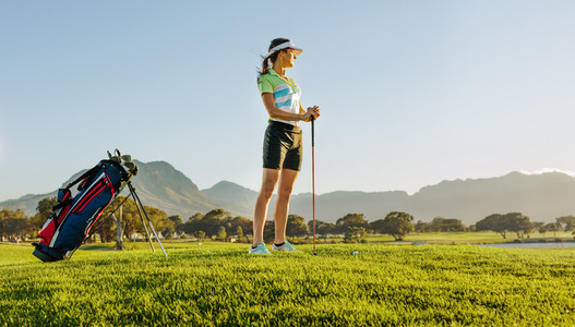 Female golfer on golf course waiting to tee off