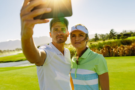 Golfers taking selfie with mobile phone
