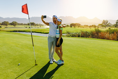 Couple of golfers making selfie at golf course