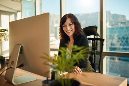 Smiling female entrepreneur sitting at her desk
