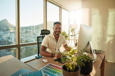 Smiling male designer sitting at his desk