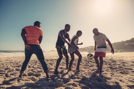 Friends enjoying a game of soccer at beach