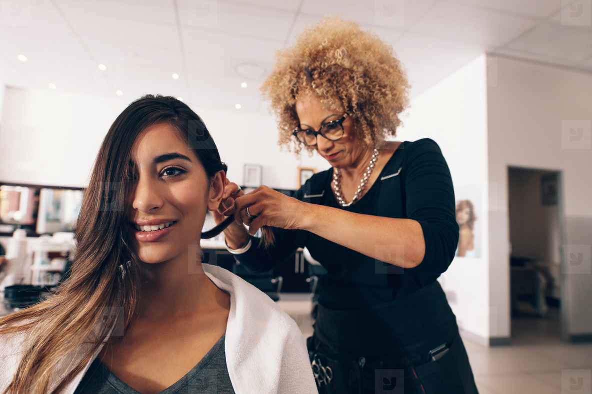 Female hair stylist working on a woman  s hair at salon