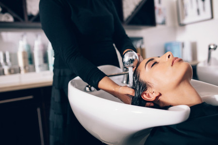Woman getting hair wash done at salon