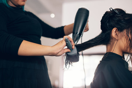 Close up of hair stylist using dryer on woman wet hair in salon