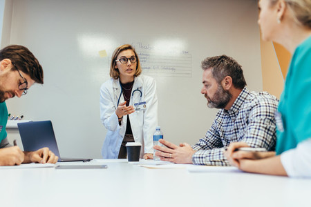 Female doctor briefing her colleagues in boardroom