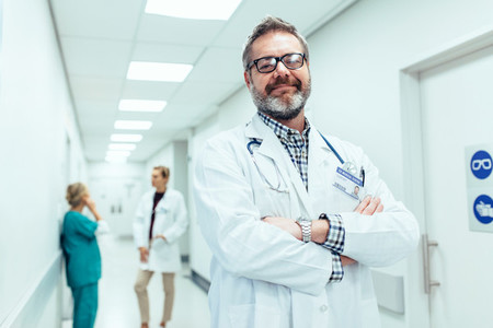 positive doctor standing in hospital hallway