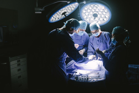 Surgeons performing surgical procedure in operating theatre