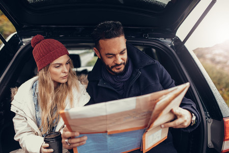 Young couple using map on a road trip