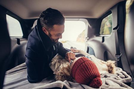 Romantic couple lying in car trunk