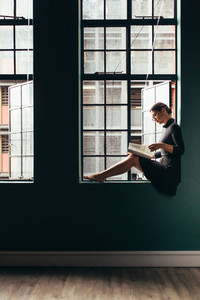 Woman on window sill reading a magazine