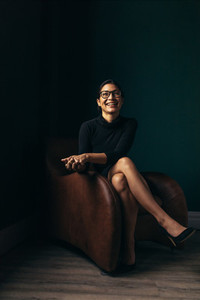 Smiling asian woman sitting relaxed on armchair