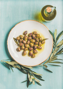 Pickled green olives olive tree branch virgin oil blue background