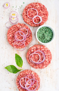 Raw ground beef meat cutlet for making burgers with onion rings and spices on white wooden background