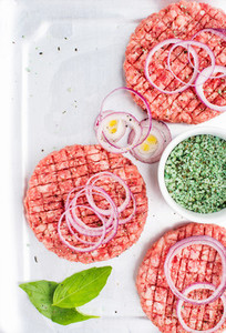Three raw ground beef meat cutlets for making burgers with onion rings and spices on white wooden background  top view