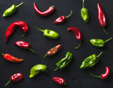 Pattern of small colorful hot chili peppers on black background