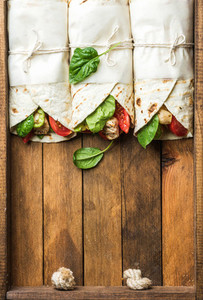 Healthy lunch snack Three tortilla wraps with grilled chicken fillet and fresh vegetables on rustic wooden tray