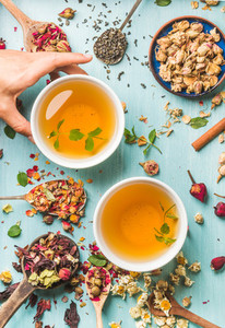 Two cups of healthy herbal tea with mint  cinnamon  dried rose and camomile flowers in different spoons  woman039 s hand holding one cup over blue background