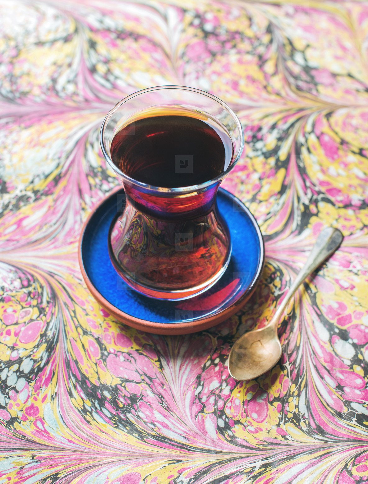 Turkish tea in traditional oriental tulip glass over colorful background