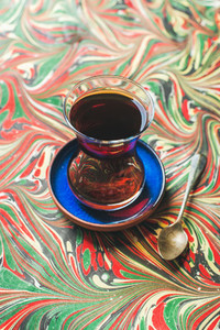 Turkish tea in traditional tulip glass and spoon  colorful background