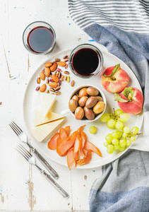 Wine snack set  Cheese  chicken carpaccio  mediterranean olives  fruits  nuts and two glasses of red on ceramic plate over white painted wooden background