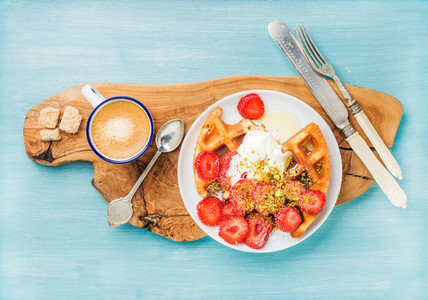 Breakfast set  Warm homemade belgium waffles with whipped cream  strawberry  maple syrup and crushed pistachios  cup of espresso  brown sugar on olive rustic wooden board over blue painted background
