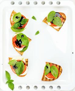 Caprese sandwiches with tomato mozzarella cheese basil and balsamic glaze on white baking tray copy space