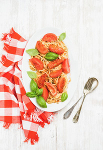 Spaghetti with roasted tomatoes and basil over white wooden background