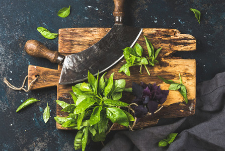 Fresh basil and vintage herb chopper on rustic wooden board