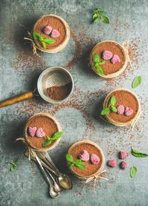 Homemade Tiramisu in individual glasses with raspberries  copy space