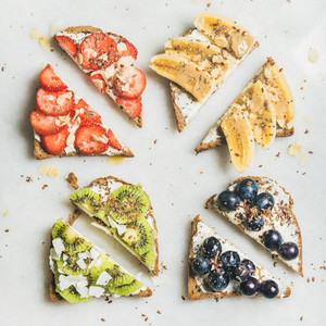 Healthy toasts with cream cheese  fruit  nuts and seeds  square crop
