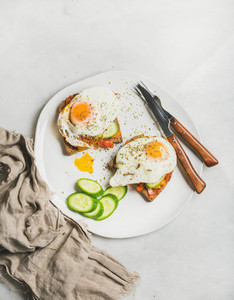 Breakfast toast with fried eggs vegetables on white plate
