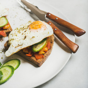 Breakfast toast with fried eggs  vegetables  square crop