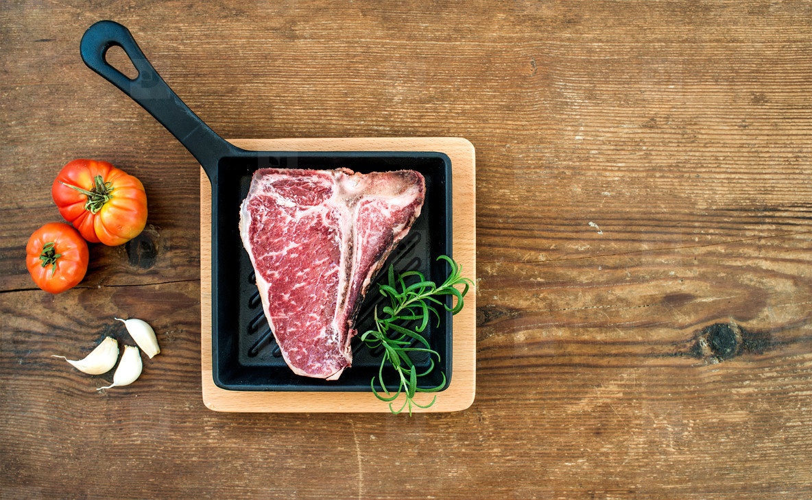 Raw uncooked meat t bone steak with garlic  tomatoes  rosemary in small dark cooking pan over rustic wooden background  top view  copy space