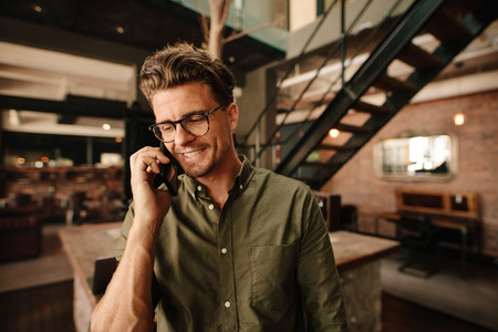 Smiling executive talking on mobile phone in office