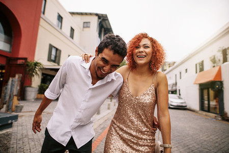 Young man and woman laughing while walking on street