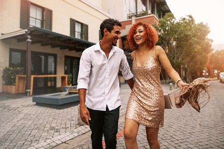 Young couple walking on street holding hand and having fun