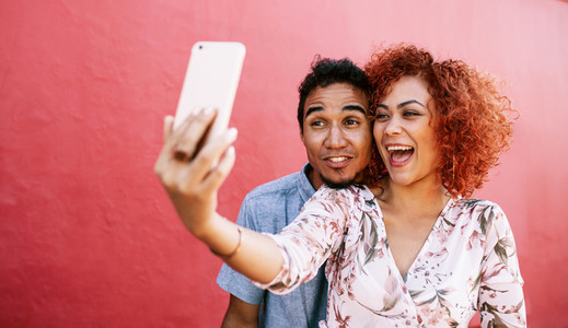 Young couple posing for a selfie using mobile phone