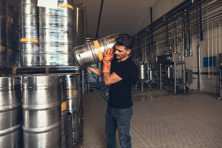 Brewer with keg at brewery factory warehouse