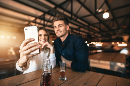Young couple sitting in the bar and taking a selfie