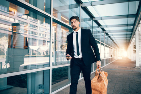 Businessman carrying bag and smart phone at airport