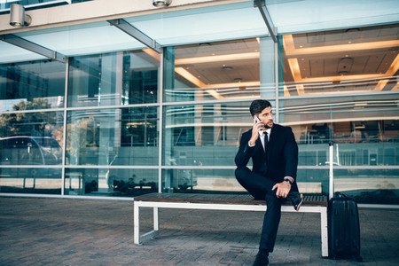 Handsome businessman sitting on bench at airport