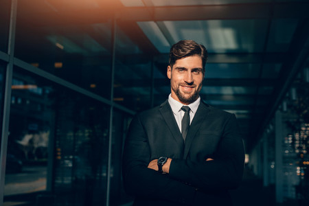 Smiling young businessman standing with his arms crossed